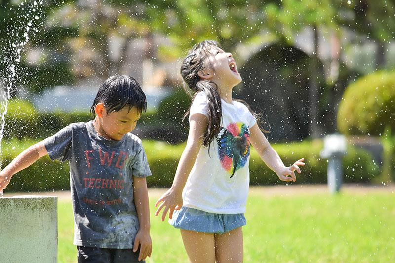 笑顔で水遊びをする子供たち